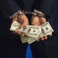 hands cuffed behind back holding money