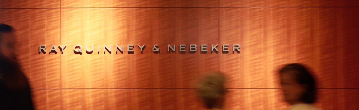 ray quinney & nebeker sign on wall with attorneys walking by