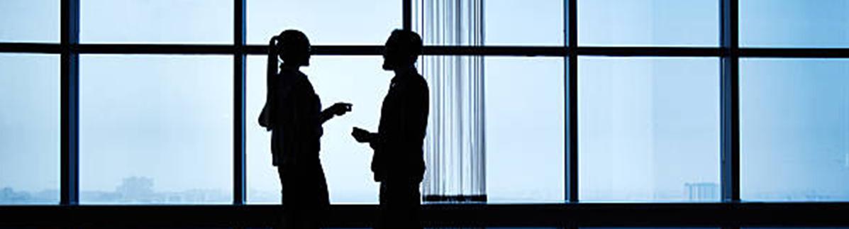 Two people talking near an office window